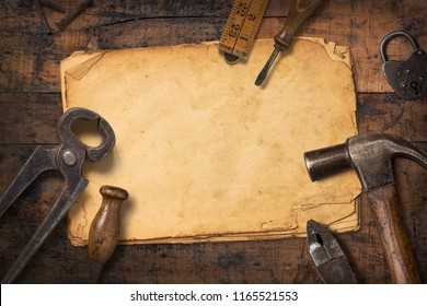 rustic masculine crafting background with vintage tools and a stack of old stained paper on a wooden desk, great for father's day, flat lay / top view