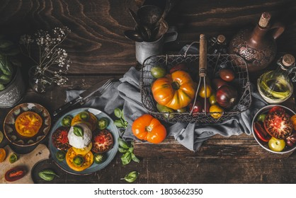 Rustic mediterran food concept with fresh harvested colorful tomatoes and mozzarella. Homemade Caprese. Seasonal food on wooden background. Top view