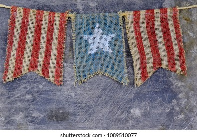 Rustic Memorial Day image of burlap flags painted with stars and stripes on worn steel background. Copy space.