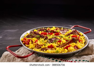 Rustic metal dish of delicious traditional Spanish paella al homo with black pudding and spare ribs on yellow saffron rice with red sweet peppers, with copy space