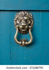Rustic metal lion head door knocker on blue painted wooden door