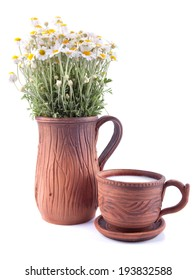 Rustic morning set from ceramic jug with flowers and cup with milk