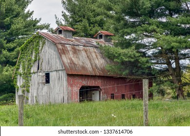 A rustic old barn with faded red paint, a rusty steep roof, and nice roof vents, stands in the countryside of rural Indiana.