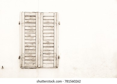 Rustic old grungy and weathered white grey wooden closed window shutters with peeling paint on a white wall of an abandoned house.