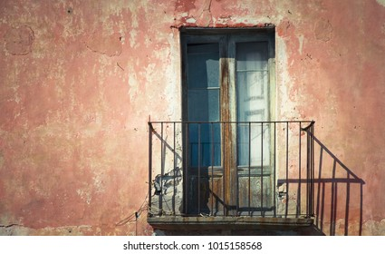 Rustic old grungy and weathered wooden closed door of rusty balcony with a red brown vintage cracked wall with peeling paint in a Southern Italy house typical facade.