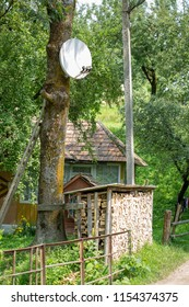 Rustic old house with a stack of chopped firewood and a satellite dish.