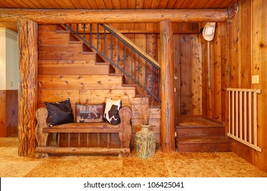 Rustic old log cabin details with staircase and wood bench.