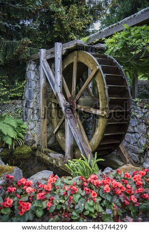 Rustic Old Milling Water Wheel In Garden Setting