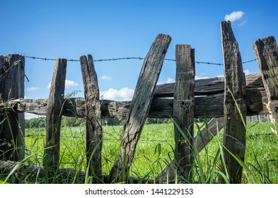 Rustic old wooden fence at the edge of a farm.
