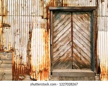 Rustic old wooden pattern door against rusty sheet metal siding
