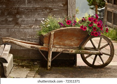 A rustic old wooden wheelbarrow filled with colorful flowers, in a rural mountain setting.
