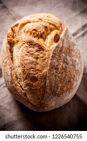 Rustic organic bread on a linen tablecloth. Top view