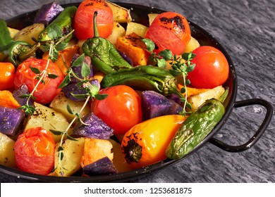 Rustic oven baked vegetables in black baking dish con gray stone background. Seasonal vegetarian vegan meal. Ingredients: potatoes, purple and sweet potatoes, tomatoes and peppers