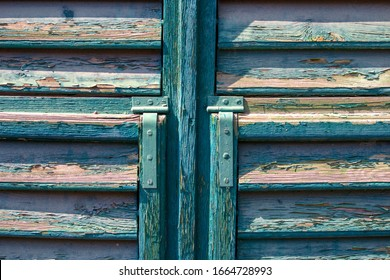 Rustic painted in green part of an old damaged wooden window or door texture. Olive green worn wooden shutter close up. Grunge design, decoration and exterior or interior details concept