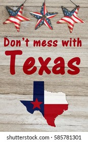 A rustic patriotic Texas message, Map of Texas with the Texas Flag colors on weathered wood background with text Don't mess with Texas