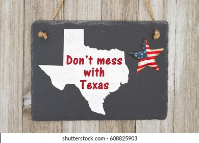 A rustic patriotic Texas message, A retro chalkboard with a vintage USA star hanging and the state map of Texas on weathered wood background with text Don't mess with Texas