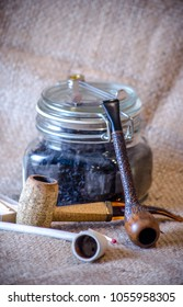 rustic pipes used by reenactors, including a clay pipe, corn cob pipe, and a hand carved artisan pipe