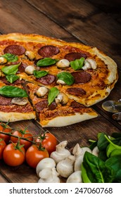 Rustic pizza with salami, mozzarella and spinach on a clay plate