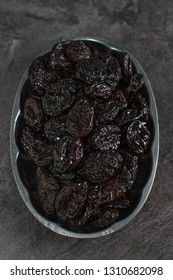 Rustic plate with  tasty smoked dried plums on table