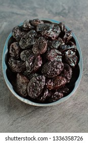 Rustic plate with tasty smoked dried plums on a dark gray background