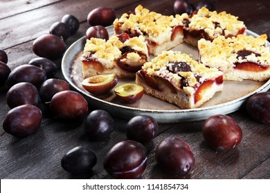 Rustic plum cake on wooden background with plums around
