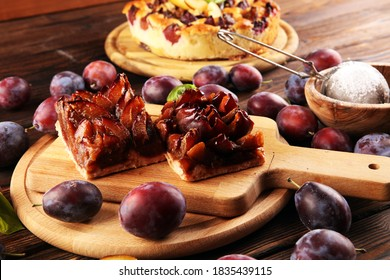 Rustic plum cake on wooden background with plums around. Plum pie concept