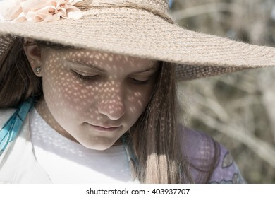 A rustic portrait of a young teenage girl wearing a straw hat and looking down. The morning sun is behind her casting a lovely pattern onto her face from the hat. A delightful horizontal format.