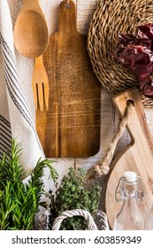 Rustic Provence kitchen interior, fresh herbs rosemary thyme, wood cutting boards, utensils, linen towel, dried peppers, glass bottles on white background, daylight