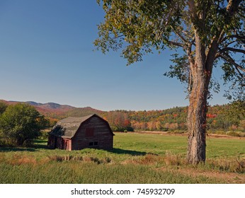 A rustic red barn with the backdrop of gorgeous fall foliage in the Adirondack Mountains, NY.