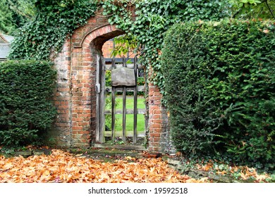 Rustic red brick Arched Gateway with fallen Autumn leaves on the ground