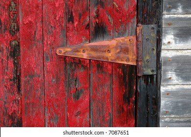Rustic red door on white shed with hinge and peeling red paint
