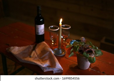 Rustic red table with romantic dinner setting, plant, wine and wine glasses, napkin and candlestick in selective focus