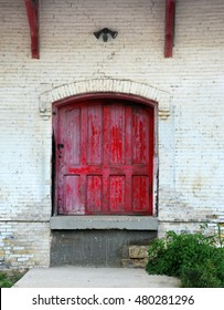 Rustic, red, wooden door is framed by white painted bricks.  Doorway is part of old train station in Stoughton, Wisconsin.