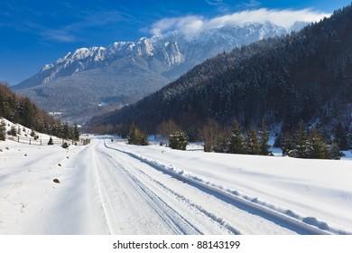 rustic road in winter, Piatra Craiului Mountains Romania