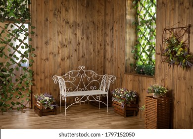 A rustic room with a wrought-iron bench, wood paneling and flowers.