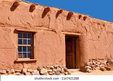 Rustic Santa Fe style adobe duilding with window door