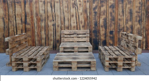 Rustic, self-made benches and a table made of euro pallets in front of a wooden wall.