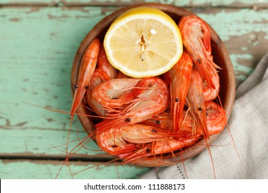 Rustic serving of cooked shrimp in a pottery bowl with lemon on a grungy painted wooden table top