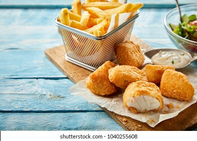 Rustic serving of crumbed fried kibbeling or bite sized portions of codfish fillet served with tartare sauce and a wire basket of French fries on rustic blue wood table