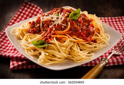 Rustic serving of traditional Italian spaghetti Bolognese topped with fresh basil and grated cheese on a modern square white plate and checkered re and white napkin