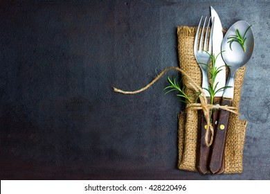 Rustic set of cutlery knife, spoon, fork. Black background. Top view
