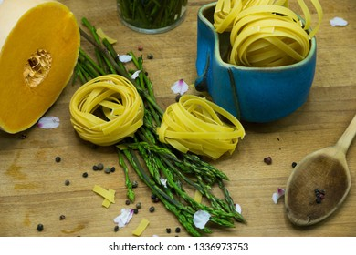 Rustic set of fresh intalian pasta with some colored vegetables, aspargus and a natural pumpkin. Preparations for a healthy dinner.