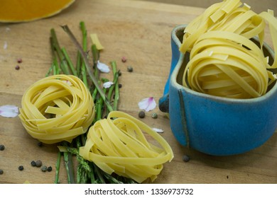 Rustic set of fresh pasta with some colored vegetables, aspargus, pumpkin, pepper and some flowers. Food for healthy and vegan people.