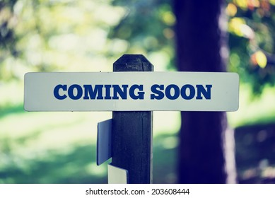Rustic signboard with the words Coming Soon proclaiming an anticipated and awaited forthcoming event outdoors in woodland.