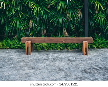 Rustic solid railway sleeper wooden bench on concrete floor on tropical green bush background.