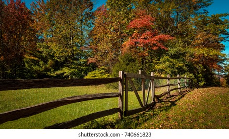 A rustic split rail fence with vibrant red fall foliage on a sunny autumn day