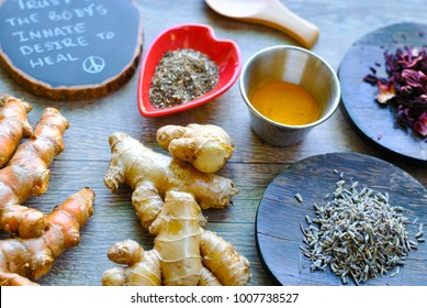 Rustic spread of healing roots and herbs for holistic health care remedies including raw turmeric root, ginger root, lavender, dried hibiscus, chia seeds, turmeric powder accompanied by healing words