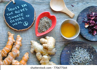 Rustic spread of healing roots and herbs for holistic health care remedies, from raw turmeric, ginger, lavender, hibiscus and chia seeds to dried turmeric all accompanied by healing words.
