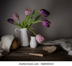 rustic still life. bouquet of tulips, fresh bread, milk on a wooden table. black background
