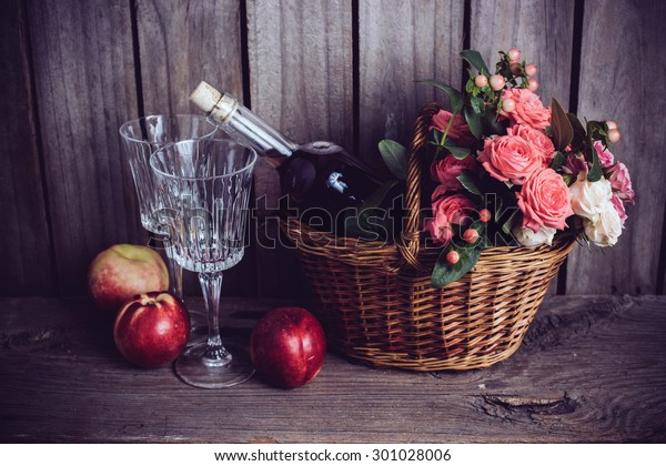 Rustic still life, fresh natural pink roses in a wicker basket  and a bottle of rose wine with two wineglasses and nectarines on an old wooden barn board background. Flowers and fruits for vintage